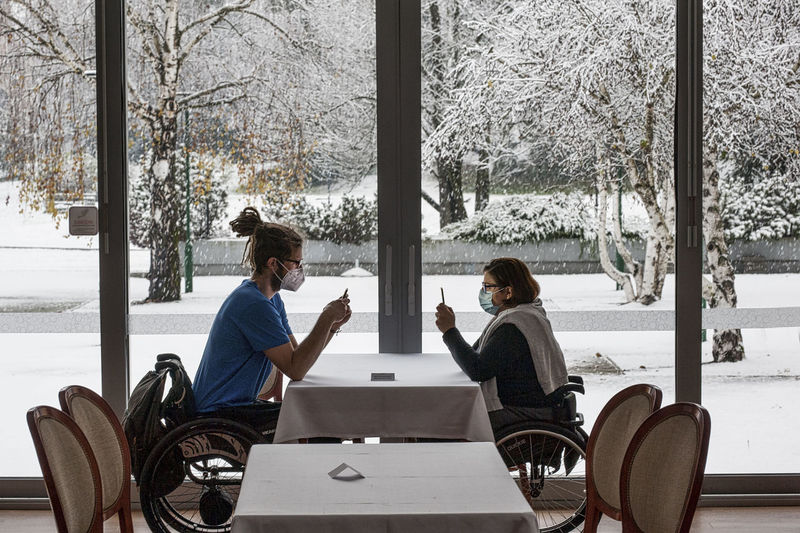 People sitting on table in park during winter
