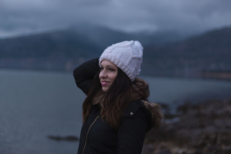 Thoughtful beautiful woman standing by lake during winter