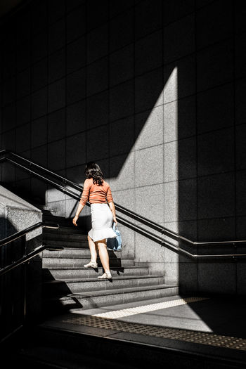 Woman in Stair Full Length One Person Shadow Staircase Women Railing Lifestyles Walking Steps And Staircases Outdoors Standing Built Structure