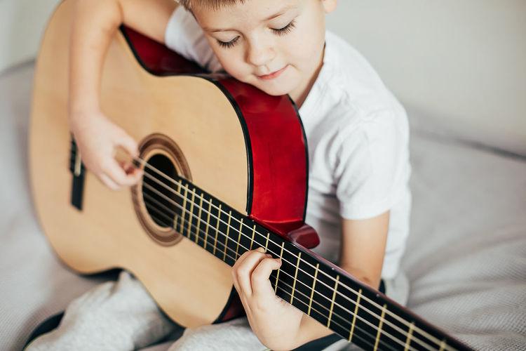 Boy playing guitar at home