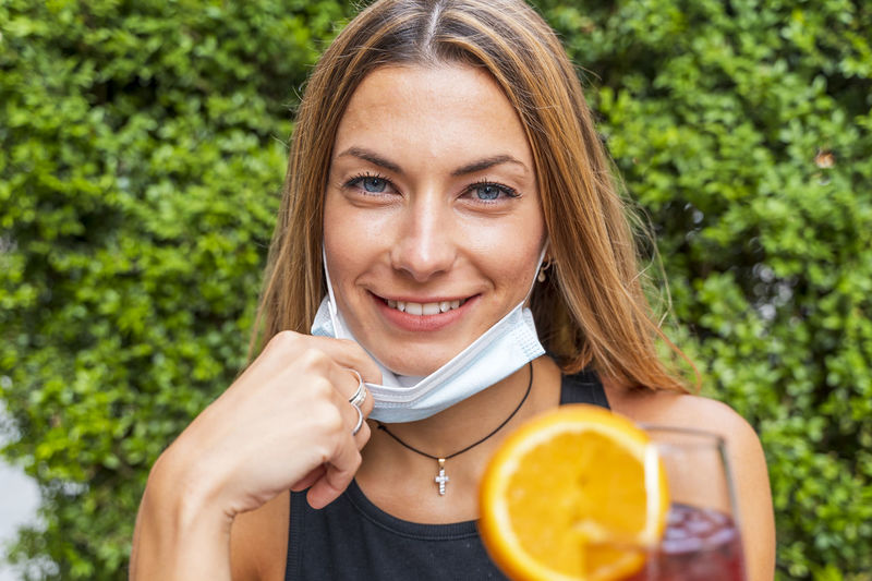Portrait of smiling young woman holding drink against plant