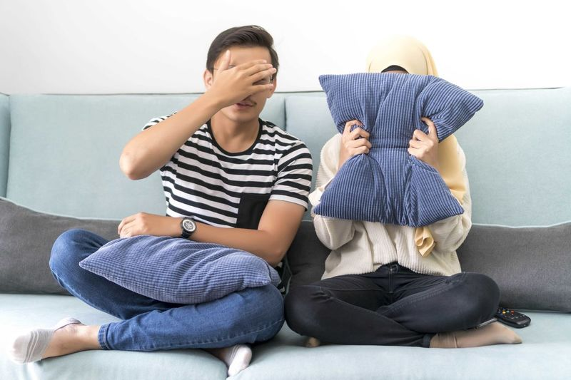 Young Malay Couple at the Sofa watching scary movie cover their eyes Sitting Full Length Child Males  Casual Clothing Men Sofa Real People Indoors  Boys Furniture Childhood Lifestyles Front View Home Interior Leisure Activity Two People Togetherness People Innocence Son