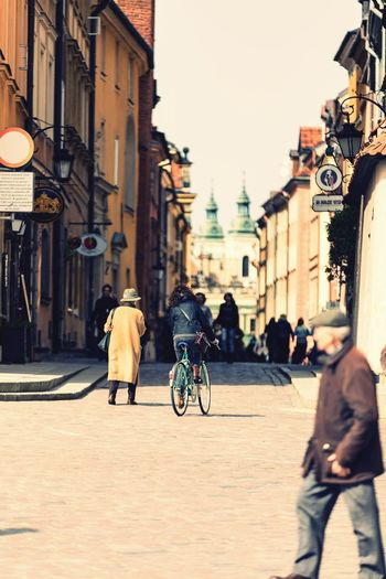 People walking on road amidst buildings against sky