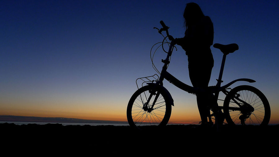 Silhouette man riding bicycle against clear sky during sunset