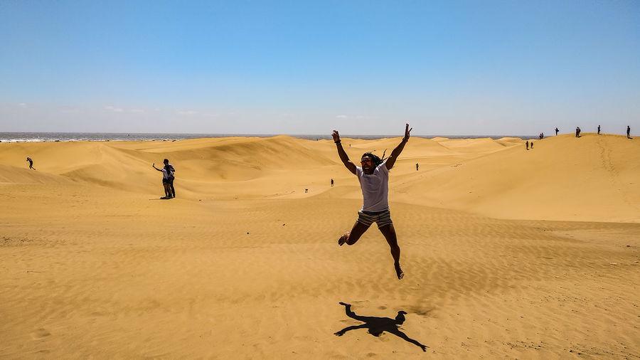 Man Jumping On Sand Against Sky At Beach