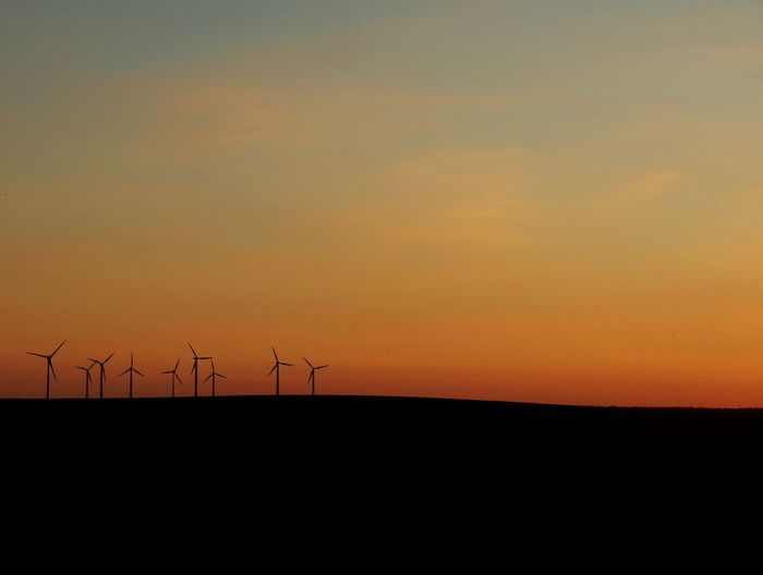 Silhouette wind turbines on field against orange sky during sunset