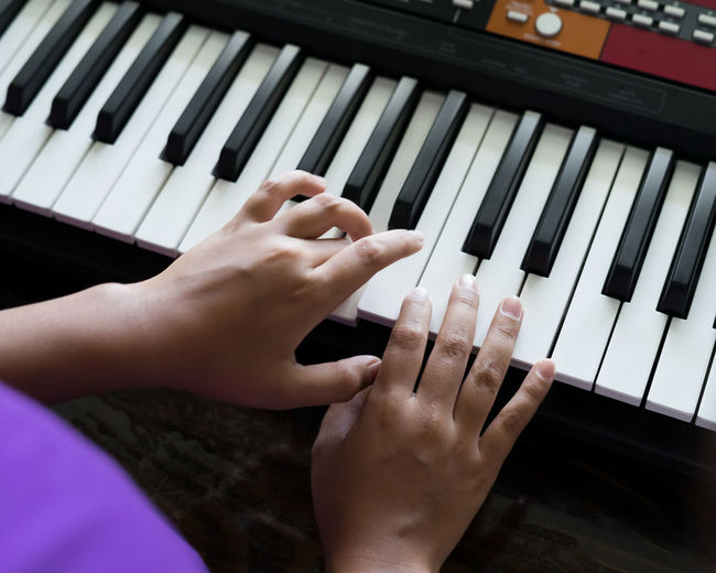 Happy cute boy playing piano at home