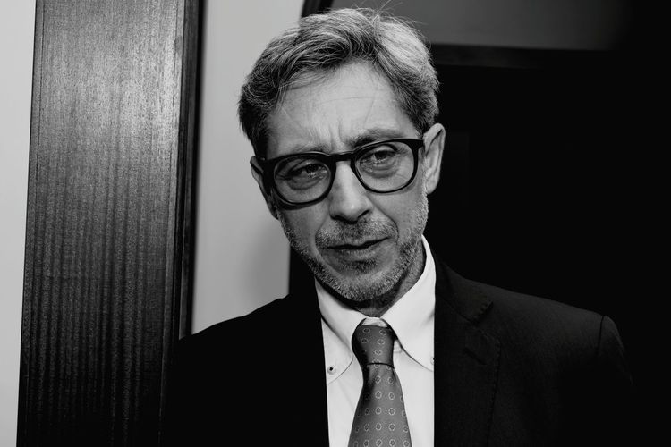 Close-Up Of Mature Man Wearing Suit And Eyeglasses Looking Away