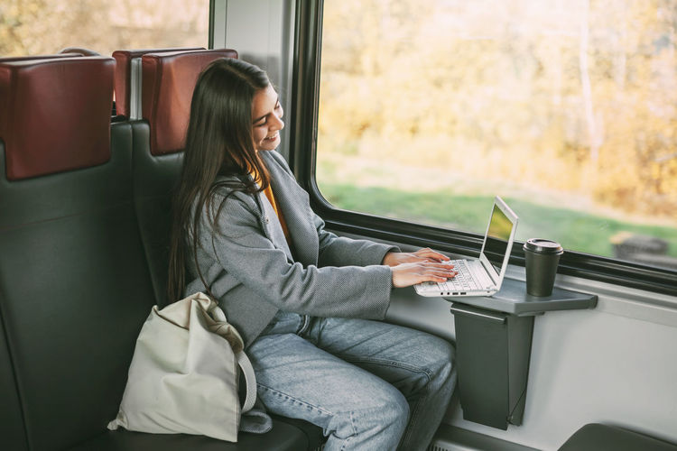 Side view of man sitting on seat in bus