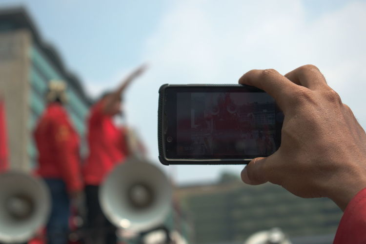 Close-Up Of Man Hand Photographing With Smart Phone In City