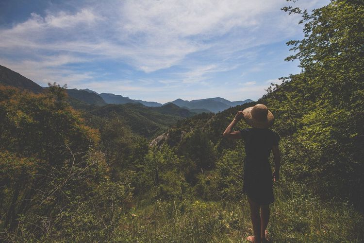 The Great Outdoors - 2017 EyeEm Awards Women Mountain Nature Sky Rear View Outdoors Scenics Beauty In Nature Sun Hat Lifestyles Landscape Standing One Person Tree Adventure Real People Hiking Day Mountain Range Forest Growth Grass