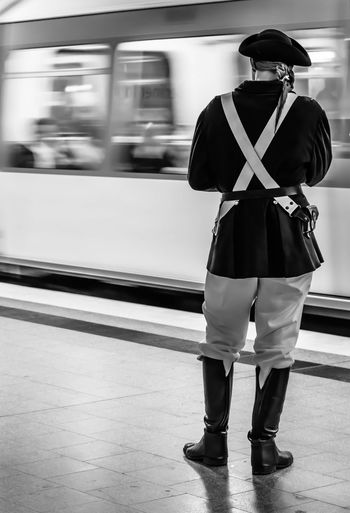 Rear view of man wearing costume at subway station