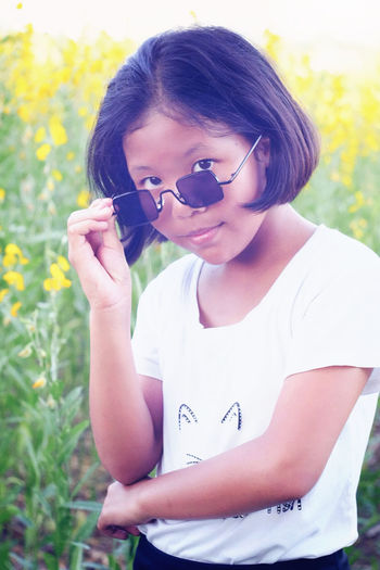 Portrait of young woman wearing sunglasses on field