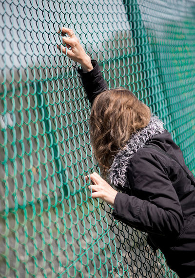 Woman looking through green chainlink fence