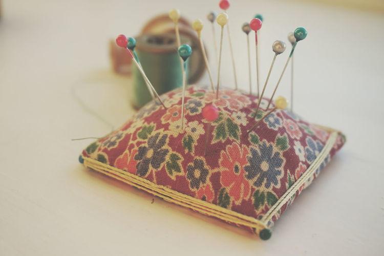 Close-up of colorful thumbtacks on pin cushion