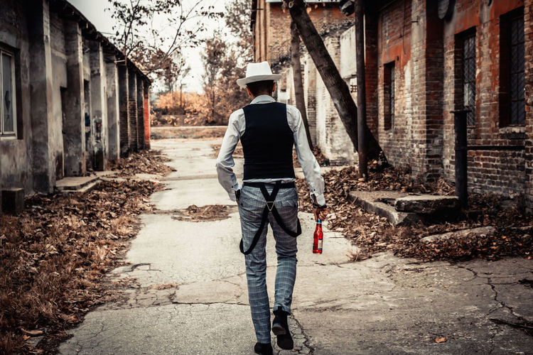 Rear view of a man holding beer bottle while walking through town street.