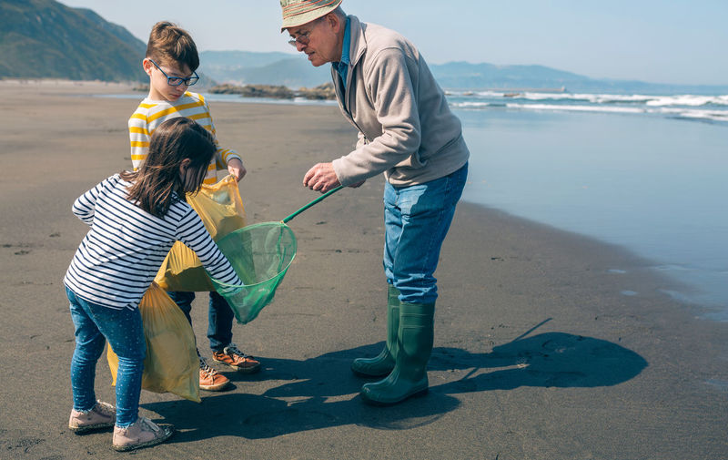 Grandfather with grandchildren cleaning beach
