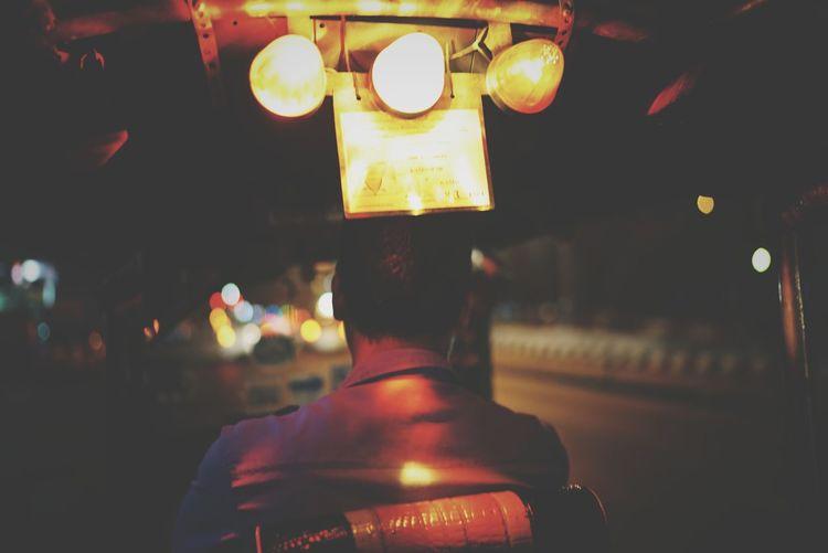 Rear view of man driving tuktuk