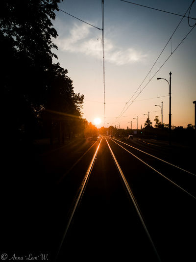 Sun setting in the city with railtrack in the foreground. Sky Sunset Transportation Electricity  Rail Transportation Sunlight Direction No People Track Diminishing Perspective Cable Power Line  vanishing point The Way Forward Silhouette Sun Railroad Track Nature Plant Power Supply Tree Outdoors Straight The Week on EyeEm EyeEm Best Shots EyeEm Masterclass Dawn Sunrise Railing Railroad Track HuaweiP9 Huaweiphotography