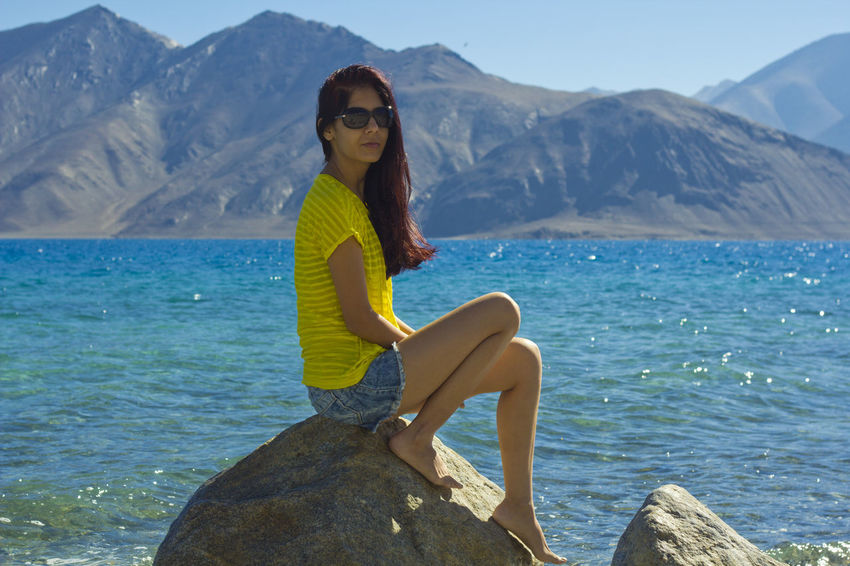 Beauty In Nature Blue Casual Clothing Idyllic Lake Leisure Activity Lifestyles Looking At Camera Mountain Mountain Range Nature Non-urban Scene Person Portrait Scenics Sea Side View Smiling Tranquil Scene Tranquility Turquoise Colored Vacations Water Young Adult Young Women