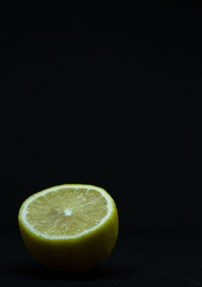 Close-up of lemon slice on table against black background