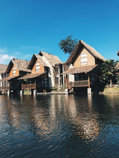 Houses by lake against buildings against clear blue sky
