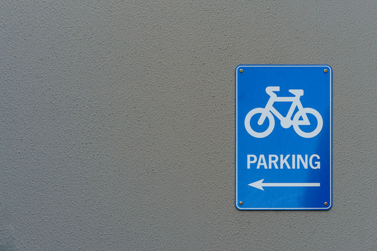 Close-Up Of Bicycle Parking Sign On Gray Wall