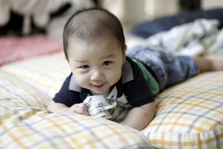 Portrait of cute baby boy lying on bed