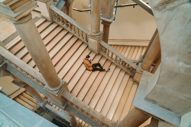 High angle view of man using mobile phone sitting on steps