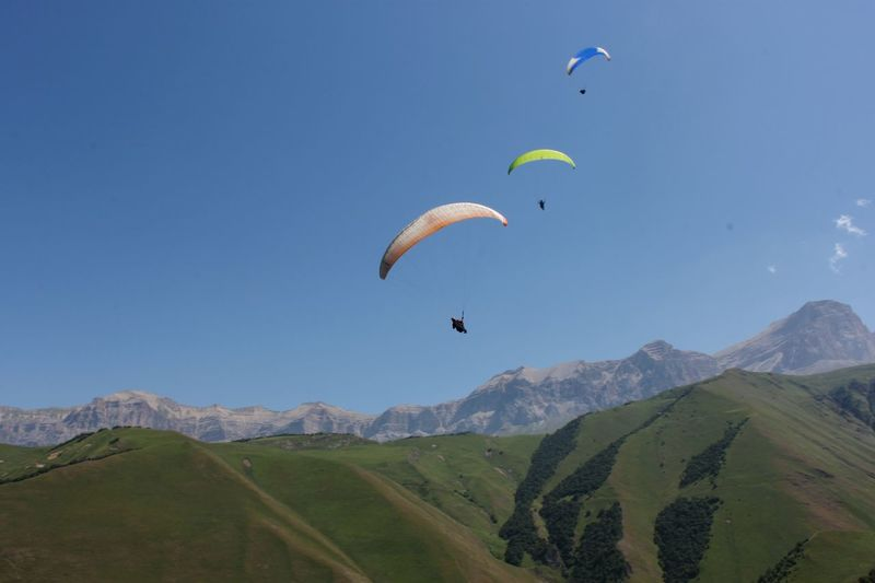 Paragliding Flying Mid-air Extreme Sports Wind Landscape Parachute Nature Sky Motion Outdoors Multi Colored Adventure Sport Vacations Jumping Scenics Physical Activity People Stunt Person Go Higher