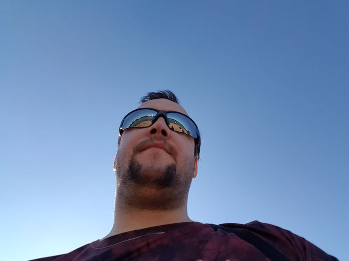 Low angle view of man against clear blue sky