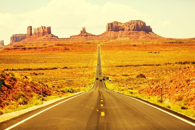 Road amidst landscape leading towards monument valley against sky
