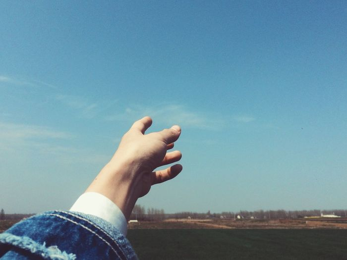 Cropped image of person pointing at sky