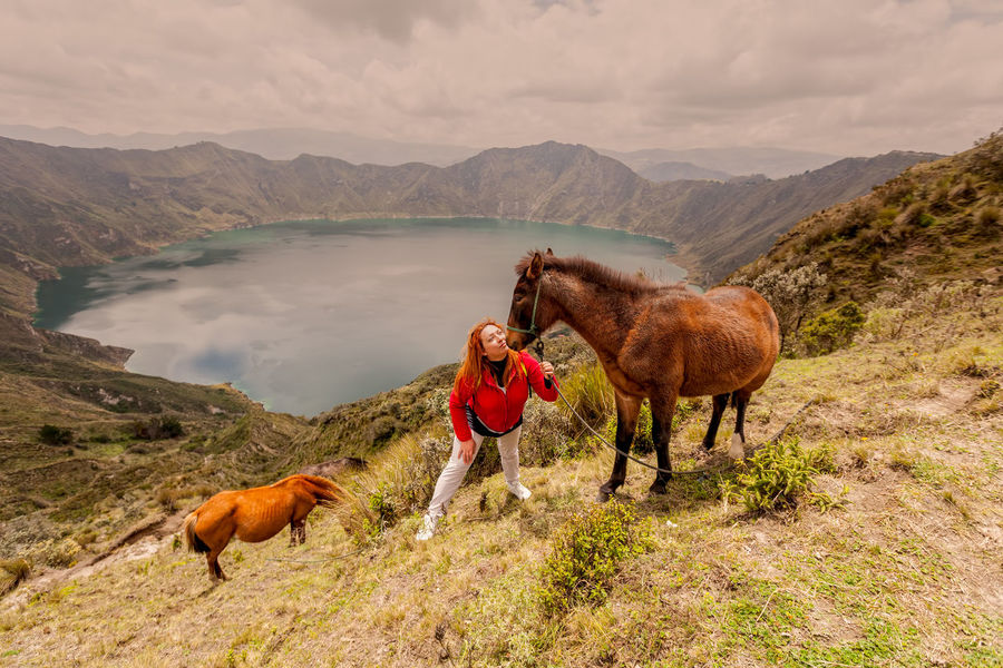 Beauty In Nature Day Domestic Animals Field Grass Horse Lifestyles Livestock Love Mammal Men Mountain Mountain Range Nature Nature One Animal One Person Outdoors People Pets Real People Sky Standing Woman Young Adult
