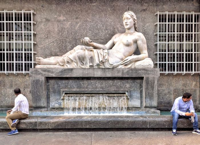 Statue of man sitting at historical building