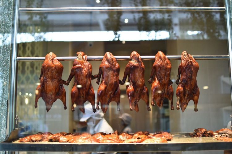 Close-Up Of Roasted Meat Hanging On Rod In Commercial Kitchen