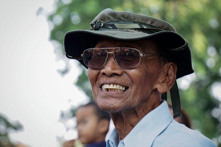 Close-up portrait of happy senior man wearing sunglasses outdoors