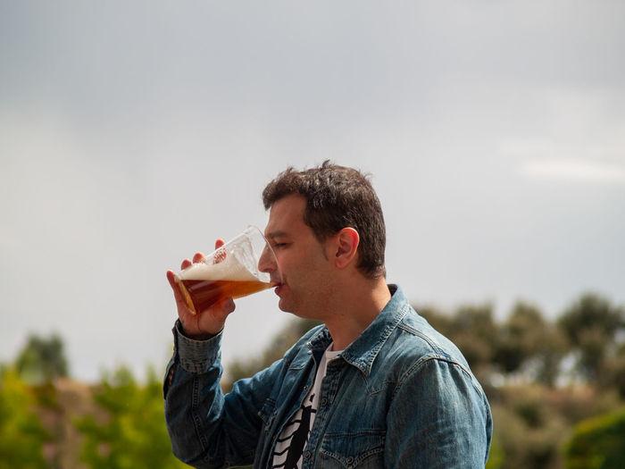 Side view of man drinking beer against sky