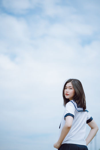 Portrait of beautiful young woman standing against sky