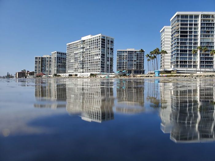 Reflection of buildings in lake against clear sky