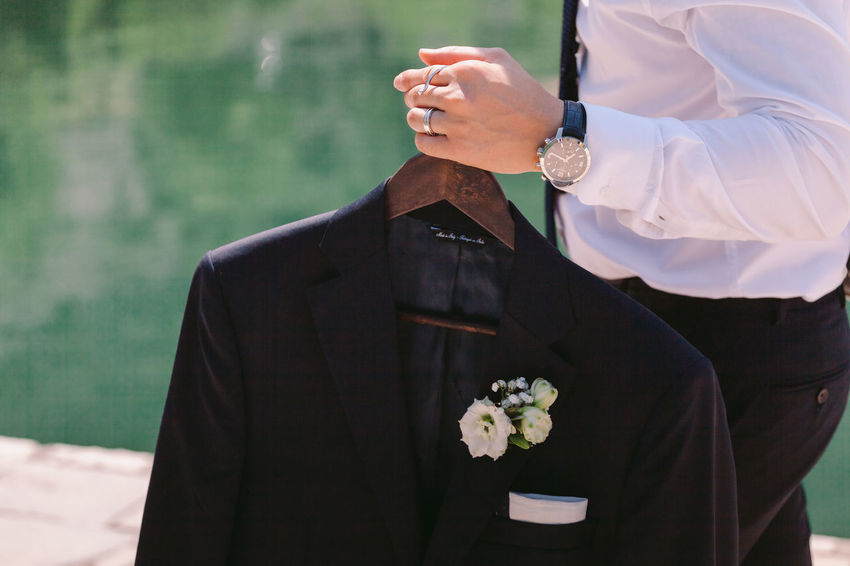 Groom holding wedding suit. wedding suit with boutonniere Groom Suit Tuxedo Black Suit Boutonniere Carry Hand Holding Male Men Outdoors Watches Wedding Ring Wedding Suit