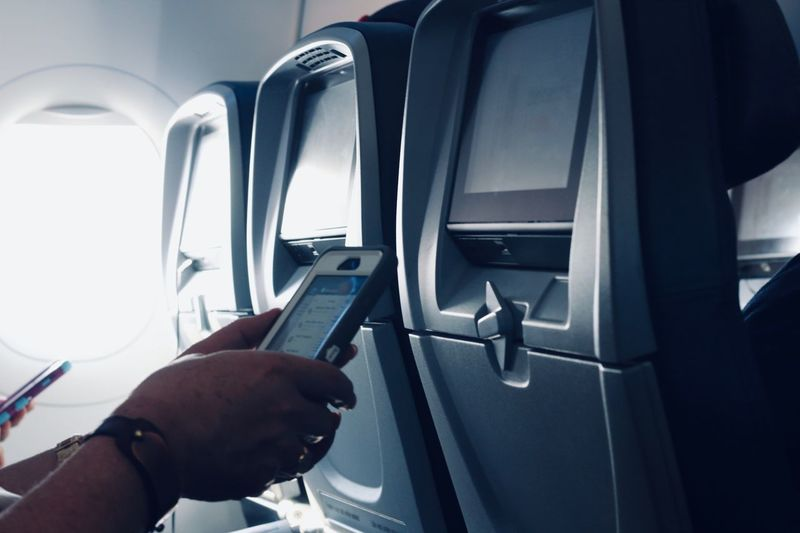 Using mobile phone in flight Human Hand Transportation Mode Of Transportation Hand Human Body Part Vehicle Interior One Person Close-up Men Travel Lifestyles Real People Technology Indoors  Communication Air Vehicle Body Part Finger Day Holding
