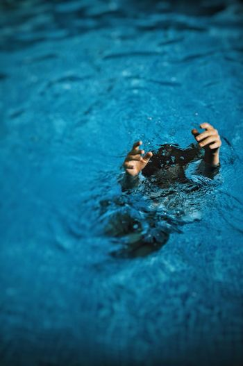 High Angle View Of Woman Drowning In Swimming Pool