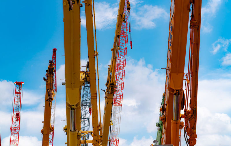 Crawler crane against blue sky and white clouds. real estate industry. red crawler crane .