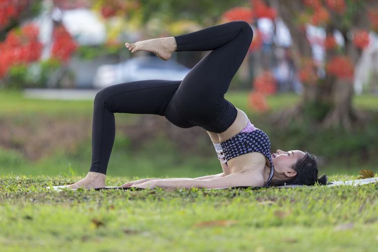 Full length of woman practicing yoga on exercise mat in park