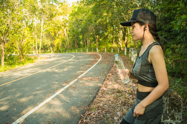 Woman Listening Music While Standing On Roadside