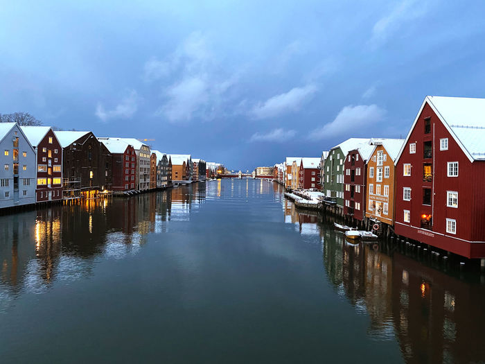 Canal amidst houses and buildings against sky