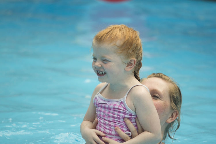 Mother holding smiling girl in swimming pool