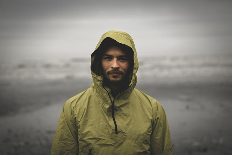 Portrait of young man standing against sea