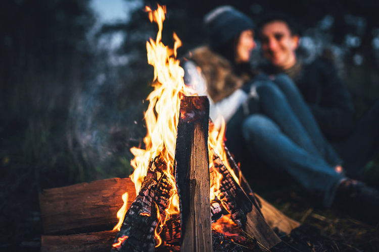 Young Couple Enjoying Campfire In Forest At Dusk